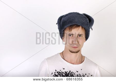 Young Man In Grey Cap With Earflaps Looks Surprised In Studio