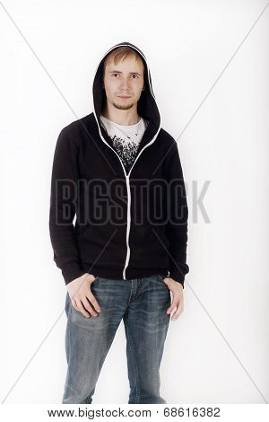 Young Handsome Man In Black Hoodies And Jeans Looks At Camera In Studio