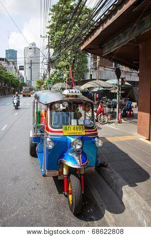 BANGKOK - APRIL 21, 2014: Tuk-tuk moto taxi on the street on April 21, 2014 in Bangkok. Famous Bangkok moto-taxi called tuk-tuk is a landmark of the city and popular transport.