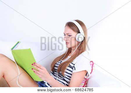 Conceptual image of  audio book. Beautiful girl with book and headphones.