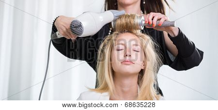 Pretty, young woman having her hair done by a professional hairstylist