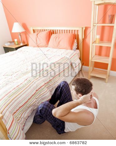 Man Doing Sit-ups In Bedroom