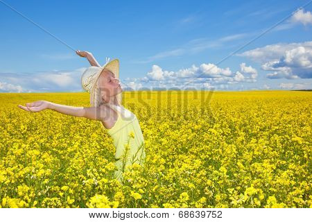 Beautiful girl enjoying the summer sun in the field.