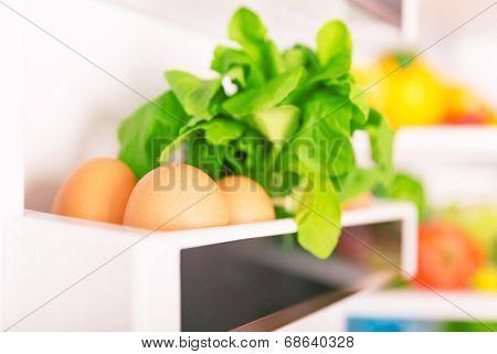 Open fridge, eggs with  fresh green rocca on the shelf of refrigerator door, organic food, healthy nutrition concept