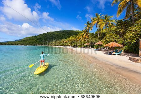 Active young woman on tropical beach vacation paddling on stand up board
