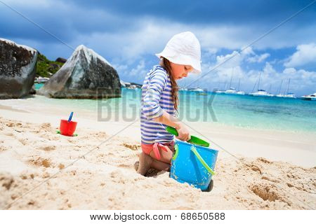 Adorable little girl wearing rash guard for sun protection at beach during summer vacation