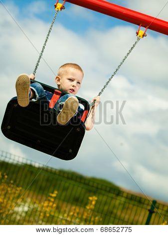 Little blonde boy having fun at the playground.