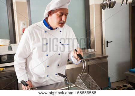 Male chef dressed in white uniform using a deep fryer