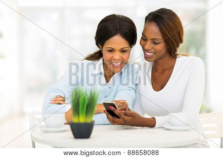 beautiful african mother and daughter using smart phone at home