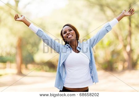 happy african woman with arms outstretched outdoors