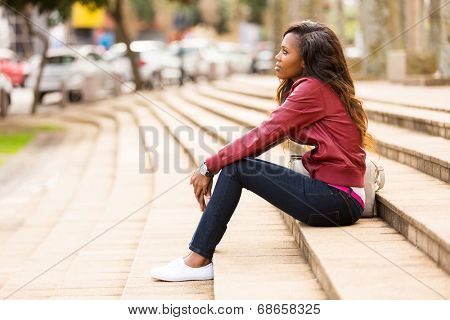 thoughtful young african woman sitting outdoors
