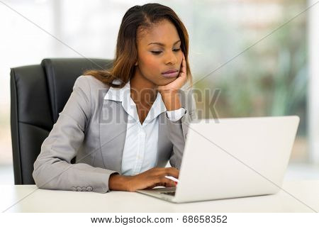 thoughtful young african businesswoman looking at the laptop screen