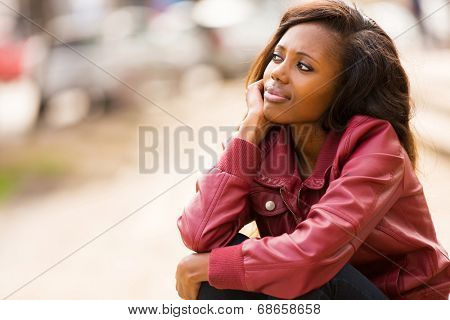 cute young african woman daydreaming outdoors