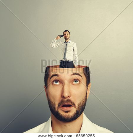 surprised man looking up at sad man with gun in his head. photo over grey background