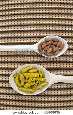Almond And Turmeric (curcuma Longa) Dry Roots  In Wooden Spoons