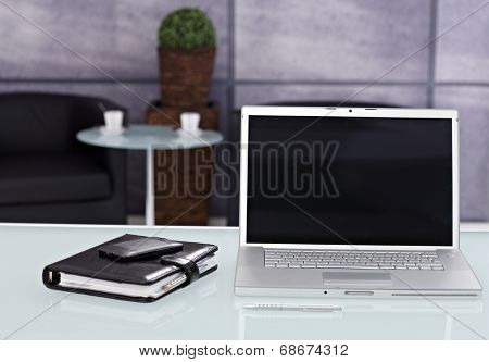Closeup photo of tidy workplace with laptop, mobile and personal organizer.