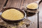 image of millet  - Portion of Millet on dark wooden background  - JPG
