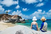 picture of virginity  - Back view of two kids sitting on granite boulder and enjoying beautiful scenery of The Baths beach area major tourist attraction at Virgin Gorda - JPG