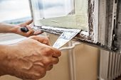 stock photo of putty  - Repairing a window frame  - JPG