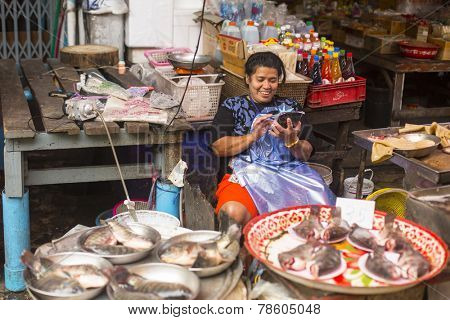 BANGKOK, THAILAND - DEC 15, 2014: Unidentified woman seller on the Burmese street market in Bangkok. There is 16,000 registered street vendors in Bangkok.