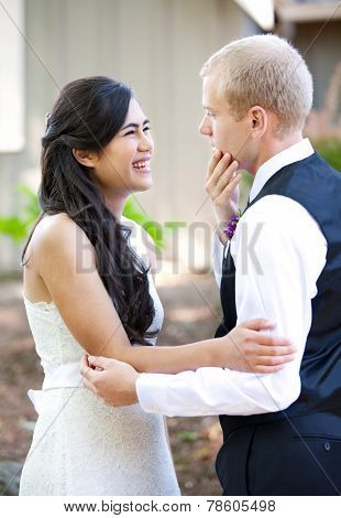 Handsome Caucasian Groom Talking With His Biracial Bride Outdoors. Diverse Couple.