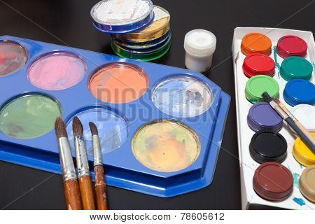 brushes and colored paint artist on gray