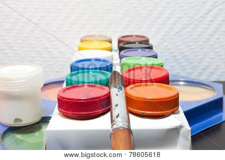 brushes and colored paint artist on white