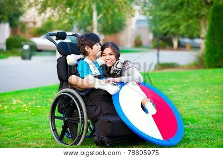 Disabled brother hugging older sister in wheelchair