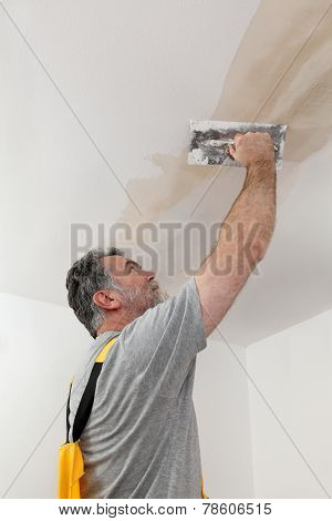 Worker Repairing Plaster At Ceiling