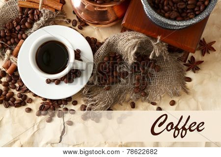 Cup of coffee, pot and grinder on beige background