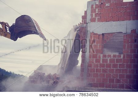 Mechanical Digger Demolishing The Wall Of A Brick Building