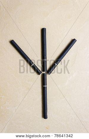 Cigarette arranged in trident shape symbolizing as a killer