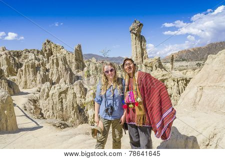 LA PAZ, BOLIVIA, MAY 9, 2014: Local man in traditional attire poses with young blond tourist in Moon Valley