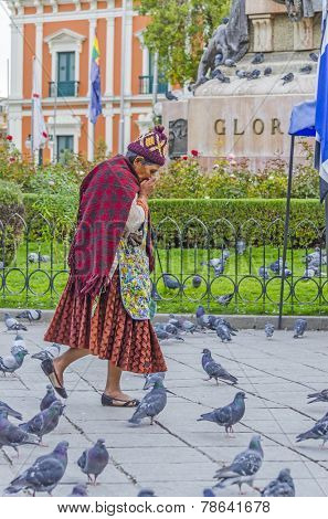 LA PAZ, BOLIVIA, MAY 9, 2014:  Local woman in traditional attire walks at Plaza Murillo
