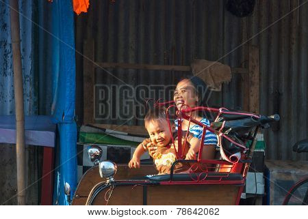 Mother With Son Enjoying A Ride In Rickshaw, Indonesia