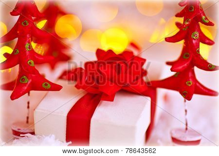 Cute little gift box wrapped in white paper with ribbon bow with small red plasticine fir tree, stylish Christmas still life