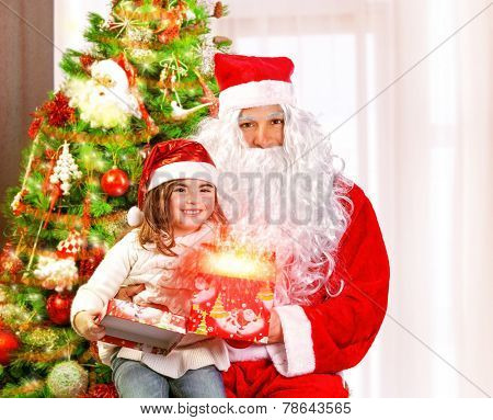 Santa Claus with granddaughter sitting near Christmas tree, cute girl opening gift box, glowing lights, magic night, fairy tale concept