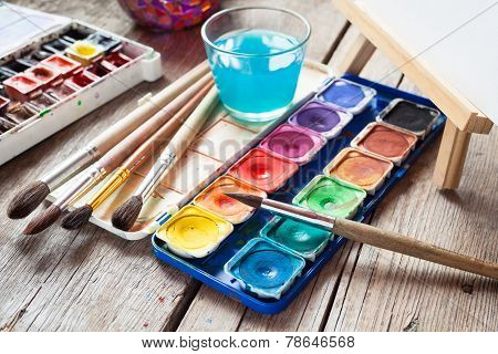 Box Of Watercolor Paints, Art Brushes, Glass Of Water And Easel With Canvas Or Paper On Old  Table.