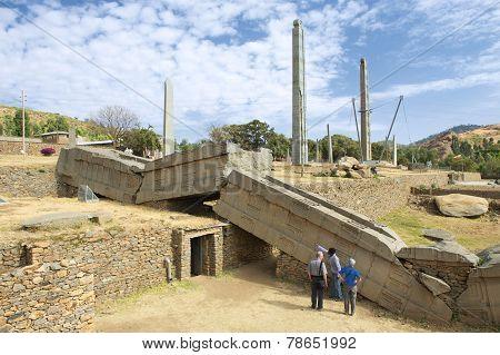 Tourists explore famous collapsed obelisks of Axum, Ethiopia.