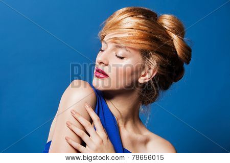 Portrait of lovely young woman with beautiful make-up and hairstyle. on blue background