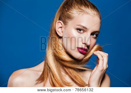Fashion photo of beautiful model with ponytail. Beauty woman on blue background