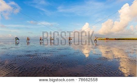 There are many fishermen are walking on the beach to work at sunrise in mekong dalta vietnam