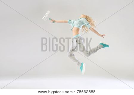 Dancing woman holding paint roller