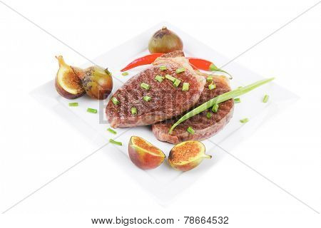 savory : grilled juicy beef pork steak served with hot cayenne peppers green chives and sweet figs on plate isolated over white background