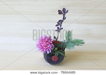 Ikebana With Pink Flower, Branches Of Blue Spruce And Barberry In The Blue-red Cup