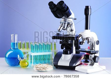 Microscopes, Petri dish with samples of grain and test tubes on table, on color background