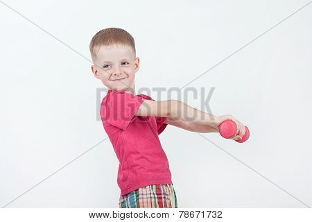 Smiling boy is doing exercises with dumbbells; isolated on the white background