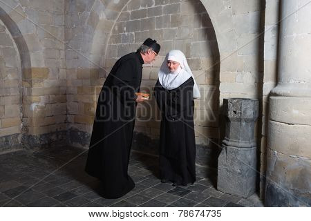 Priest and nun telling gossip in the corners of a medieval church