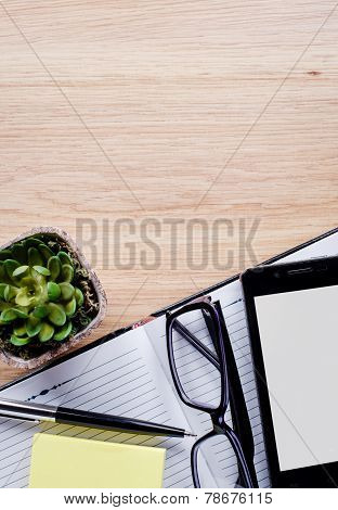 Flower Pot, Glasses, Ballpoint Pen And Notebook On The Desktop