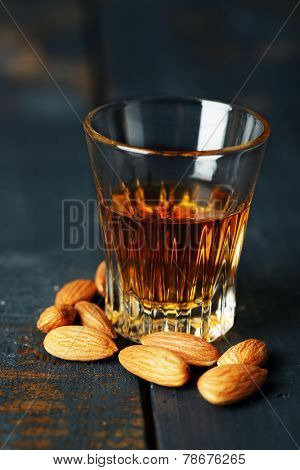 Dessert liqueur Amaretto with almond nuts, on dark wooden table